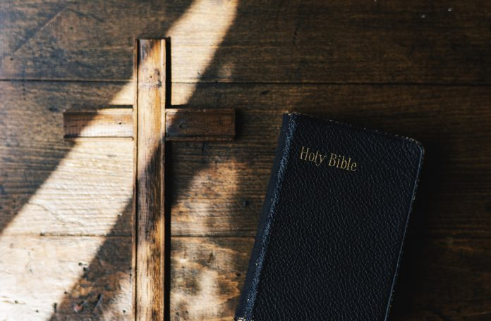 Cross and Holy Leather Bible on Wooden Background