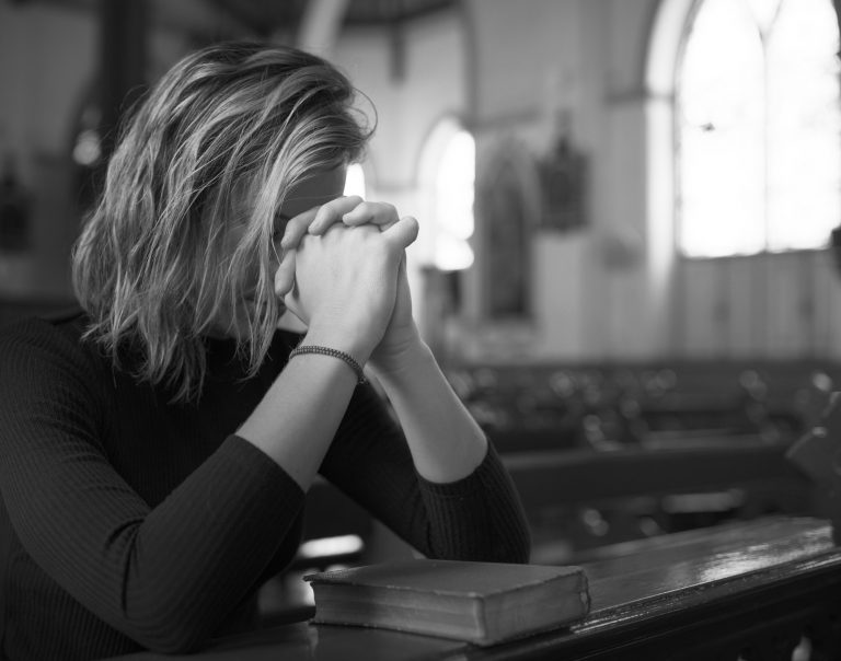 Woman praying in the church grayscale